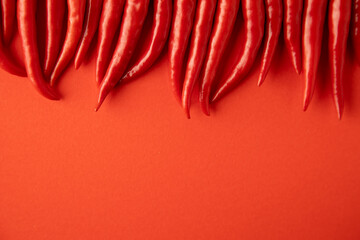 spicy red chili pepper on red background