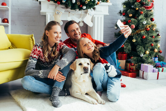 girl taking selfie with joyful parents and dog in decorated living room