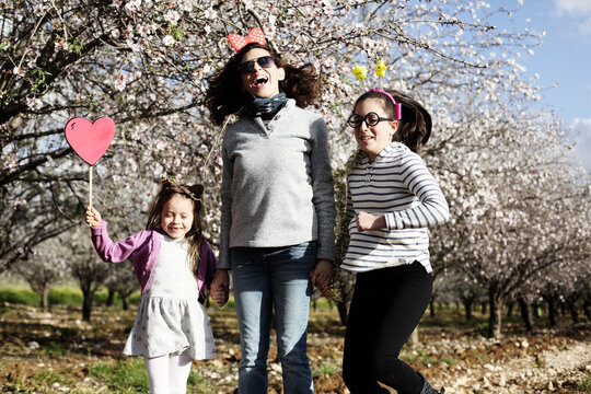 Mom and two daughters have fun in carnival costumes outdoors