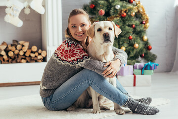 happy woman in sweater sitting on floor with labrador near decorated christmas tree