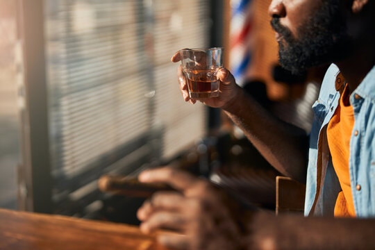Bearded young man smoking cigar and drinking whisky