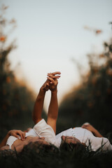Young couple lying on green lawn while spending time together in park. Romantic atmosphere. They...
