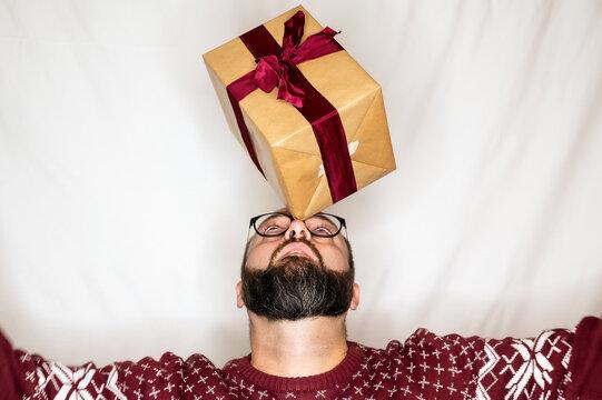 A man balances a present on his nose
