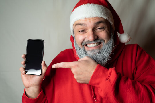 santa claus found something on his cell phone and is laughing his head off