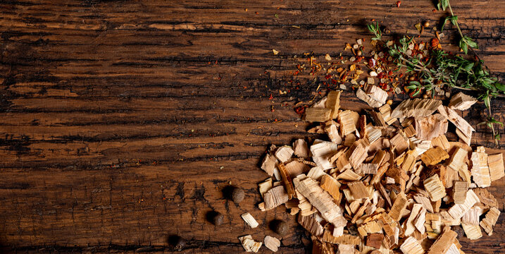 Wood chips for smoking, spices and herbs on an old wooden table top view. Free space for text.
