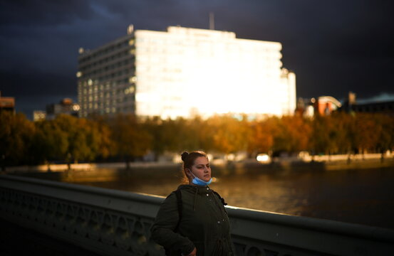 A woman wearing a protective face mask walks across Westminster bridge, during the coronavirus disease (COVID-19) outbreak, in London
