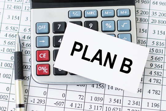 PLAN B word on a card on the desktop on a calculator, a pen and financial reports. Business concept