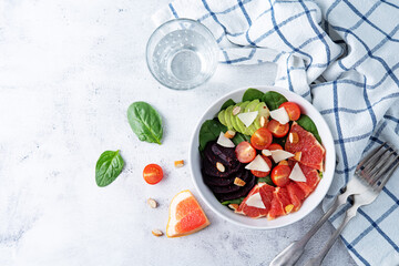 Red grapefruit beet spinach tomato salad in a bowl