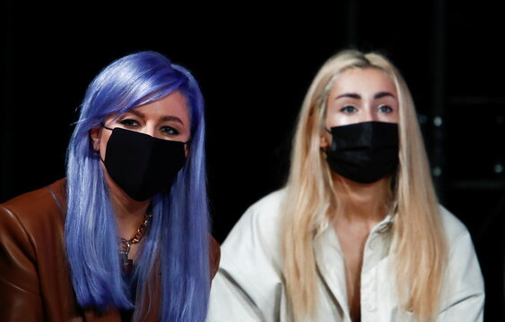 Women wearing protective face masks watch a fashion show during Mercedes-Benz Fashion Week Russia amid the coronavirus disease outbreak in Moscow