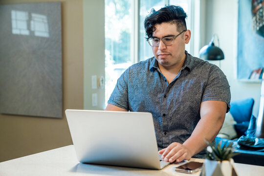 Man working from home on laptop computer sitting at kitchen counter