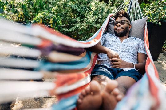 Black man napping in hammock in back yard