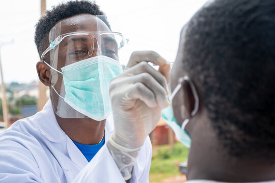 african lab scientist taking nasal sample from a man