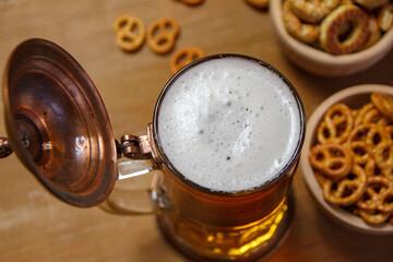 Obraz Piwo w starym, rustykalnym kuflu i precle na drewnianym blacie - fototapety do salonu