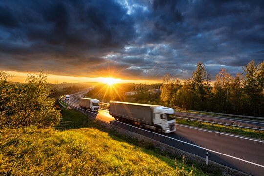 Three motion blurred trucks driving on the asphalt highway in forested landscape in the golden rays of the sunset with dark cloud