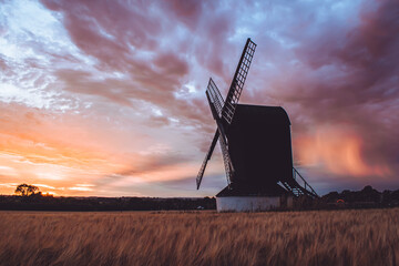 Pitstone, United Kingdom - 31 July 2020: Stunning sunset landscape view for Pitstone Windmill with dramatic cloudy sky and beautiful colors of sun setting in red and orange