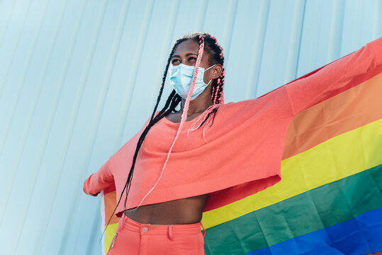 Young black gay woman with face mask holding a gay pride rainbow flag - lgbt freedom concept - Focus on girl's face