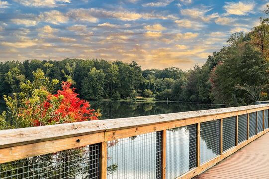 a stunning shot of a wooden bridge over a lake with lush green and autumn colored trees reflecting off the lake at sunset at Rhodes Jordan Park at Lawrenceville Lake in Lawrenceville, Georgia