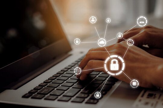 Business, technology, internet and networking concept. Young businesswoman working on his laptop in the office, select the icon security on the virtual display.
