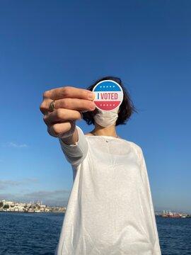 woman with mask holding i voted badge photo