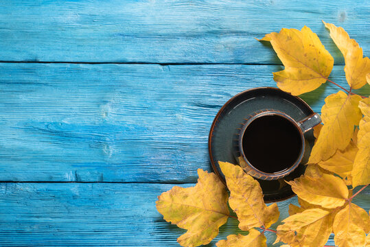 Black coffee in the cup and autumn yellow maple leaves on the blue top view background with copy space.