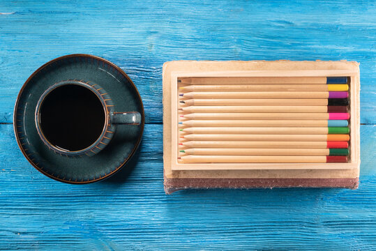 Colorful pencils and black coffee cup on the blue desk flat lay background.
