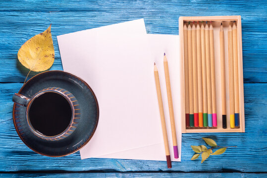 Blank paper page with copy space, colorful pencils and black coffee cup on the blue desk background.