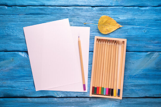 Blank paper page with copy space and colorful pencils on the blue desk background.