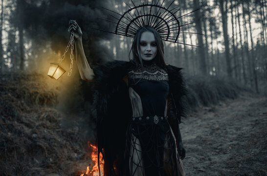 Woman in image of witch stands with glowing lamp against black smoke and fire in forest.