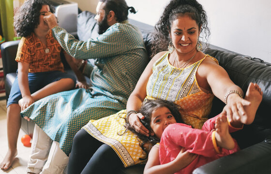 Indian family having fun at home sitting on sofa - Soft focus on mum face