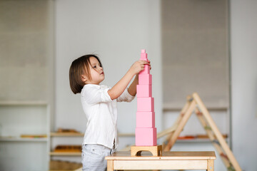 child girl playing with pink tower, developing sensory activities in montessori and earlier child development, kids independence