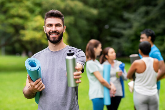 fitness, sport and healthy lifestyle concept - happy smiling young man with mat and bottle over group of people meeting for yoga class at summer park