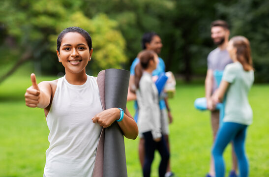 fitness, sport and healthy lifestyle concept - happy smiling young african american woman with mat showing thumbs up over group of people meeting for yoga class at summer park