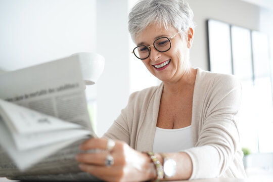 Portrait of smiling mature woman at home reading newspaper