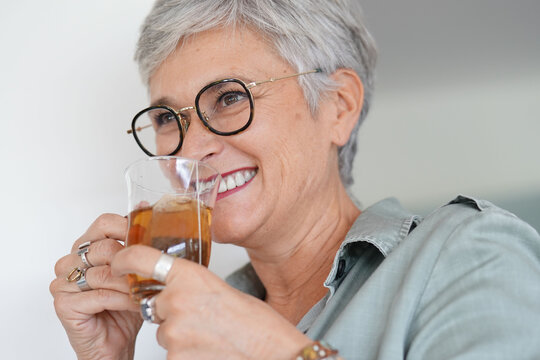 Cheerful 50-year woman drinking hot tea at home
