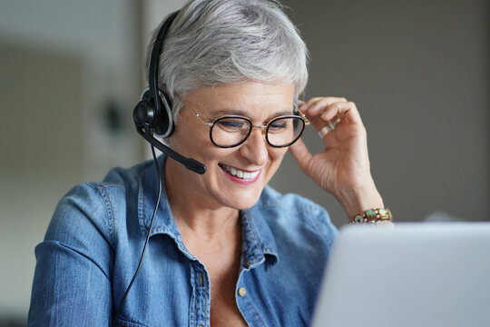 Mature woman with grey short hair working from home during pandemia