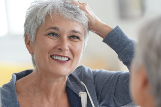 Senior woman with short grey hair putting make-up on