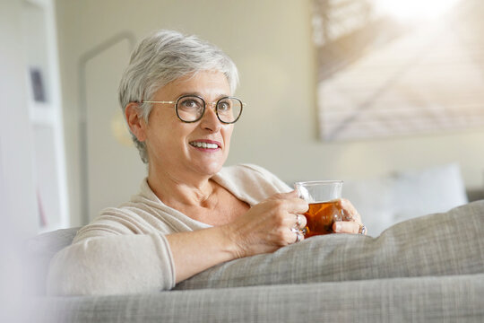 Mature woman drinking hot tea, relaxing time at home