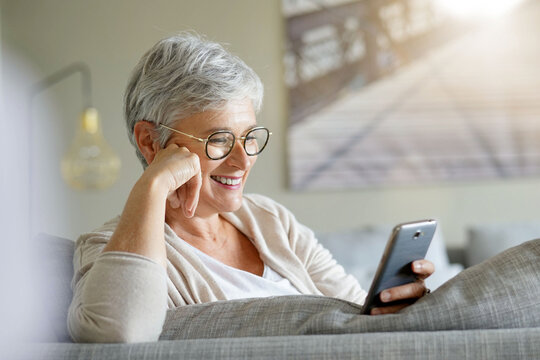 Mature woman with white short hair and eyeglasses connected with smartphone