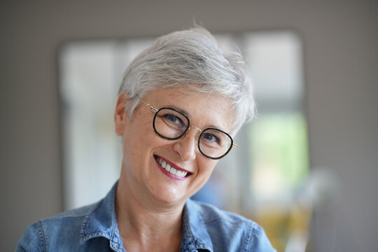 portrait of a beautiful smiling 50-year-old woman with white hair