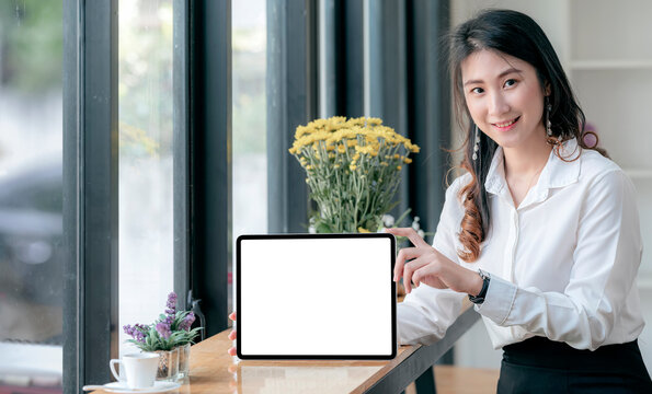 Portrait of young asian woman showing blank screen tablet, smiling and looking at camera.