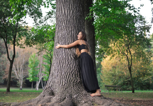 young woman hugs a tree in a park