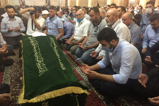 Relatives of Sunni Muslim Mufti Sheikh Mohammed Adnan Afiouni read the Quran during his funeral at Umayyad mosque in Damascus