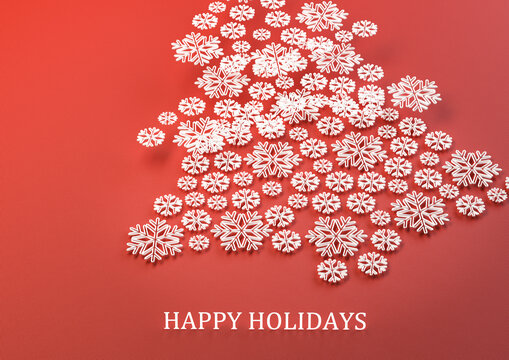 "Christmas tree made from white snowflake models in three layers on top of a red fabric background. Text ""Happy Holidays"" at the bottom."