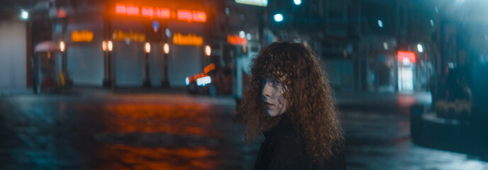 Woman with curly hair in a white shirt and black jacket walks down the red lighting street at the night and turns and looks the back camera - Fashion clothing and feminism concept Fotomurales
