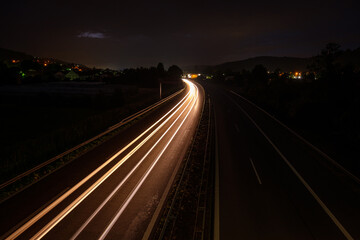 White car light trails on a motorway in night
