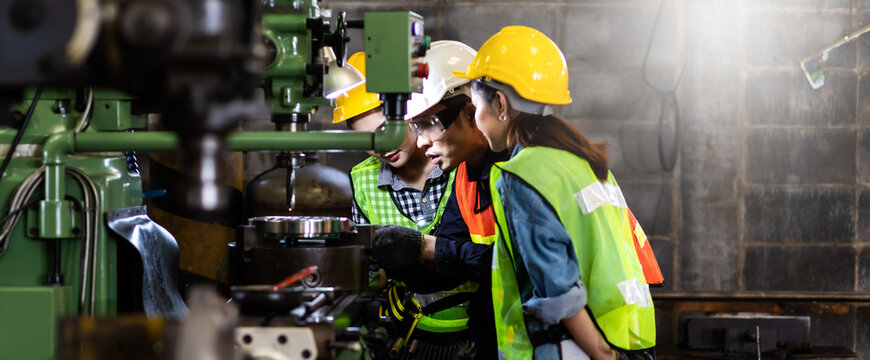 Asian Factory worker training to colleague on production line in Heavy Industry Manufacturing Facility. Instructor with Trainee working at factory.