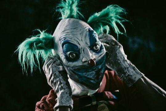 disturbing evil clown wearing a face mask