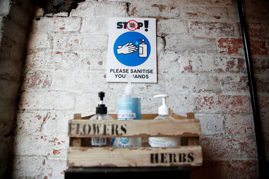 Hand sanitizers and a sign are pictured at The Farm Fresh Market, a farm shop that has offered free lunches to children who need it over half term, as the spread of coronavirus diseases (COVID-19) continues, in Watnall, Nottingham