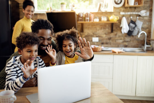 Happy black family making video call over laptop and waving to someone.