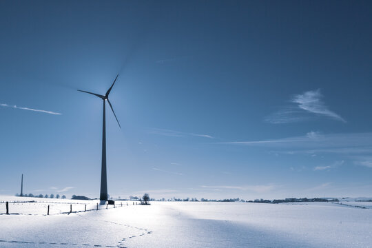 Wind Turbine in winter on a field with sunflare and shadows of the blades